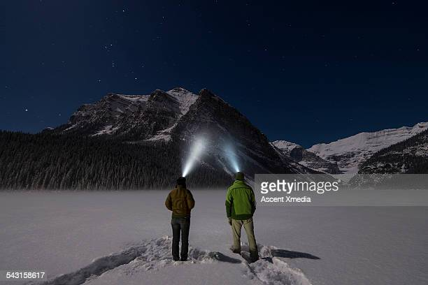 Couple stand in snowy mtn clearing, with headlamps