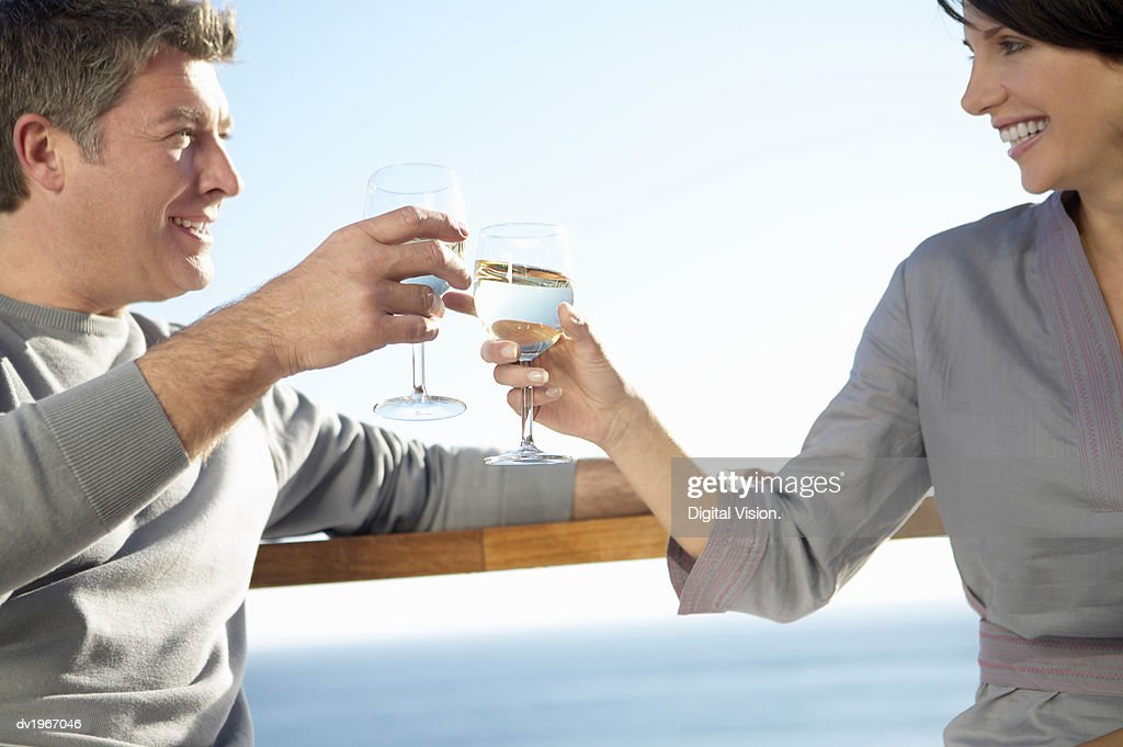 Couple Stand on a Balcony Making a Toast With Glasses of White Wine : Stock Photo