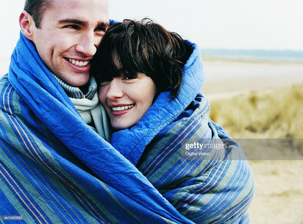 Couple Stand on a Beach Wrapped in a Blanket Together : Stock Photo