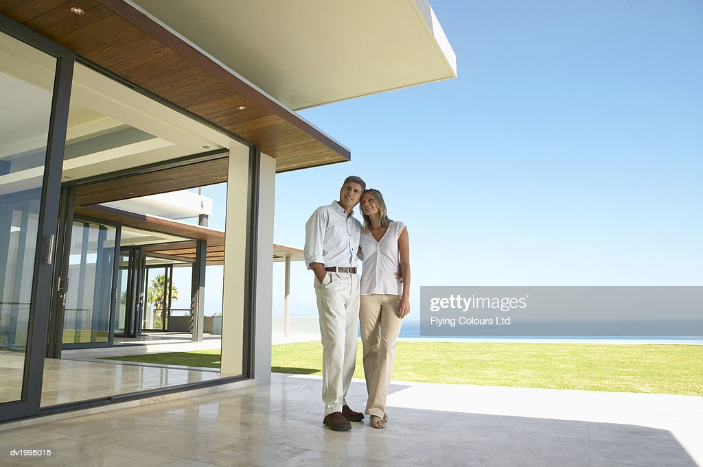 Couple Stand on a Patio Admiring Their Holiday Home by the Sea : Stock Photo