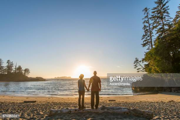 couple stand on beach log, look out to sea - vancouver island stock pictures, royalty-free photos & images