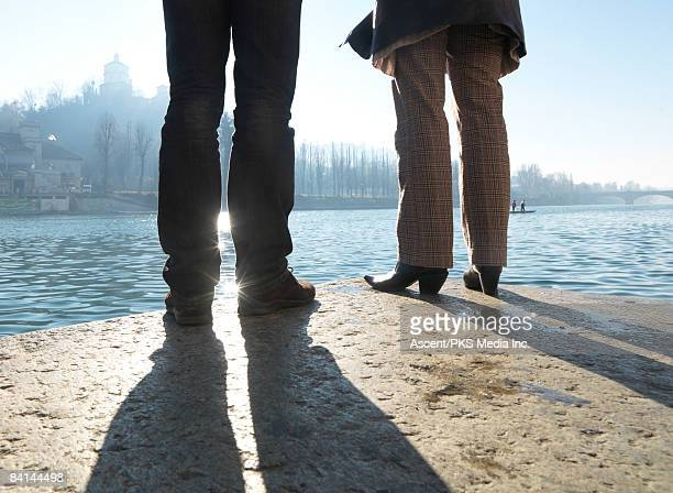 Couple stand on granite slab, look across Po River