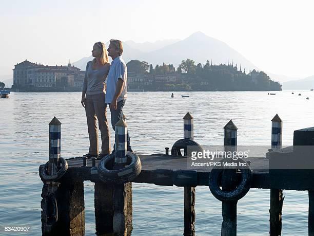 couple stand on pier, look out, isola bella behind - partire bildbanksfoton och bilder