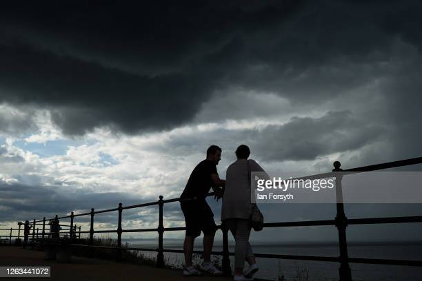 A couple stand on the upper promenade as thunder clouds pass overhead on August 02 2020 in Saltburn By The Sea England Heavy showers have continued...