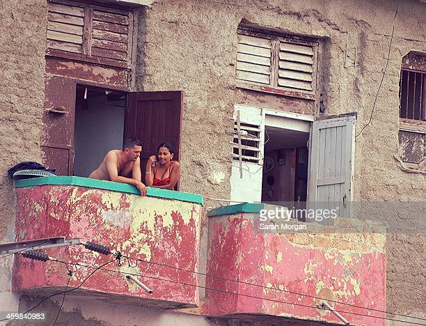 Couple stand on their balcony in Havana, Cuba. Many of the buildings in Centro and Old Havana are in a state of decay with crumbling brickwork. It is...