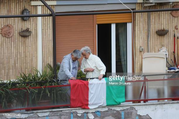 A couple stand on their balcony on March 22 2020 in Rome Italy As Italy extends its nationwide lockdown to control the spread of COVID19 its citizens...