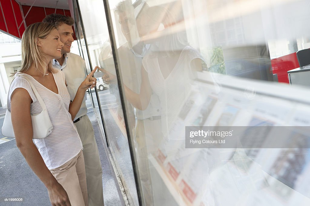 Couple Stand Outside an Estate Agents Looking at the Window Display : Stock Photo
