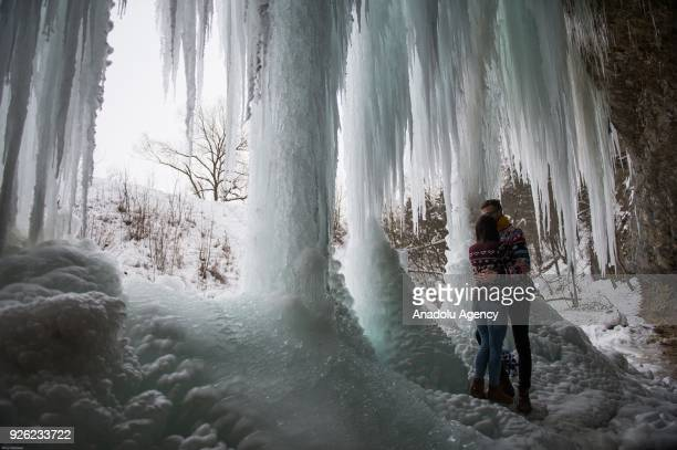 A couple stand under the icefall Siklava Skala in Spisska Nova Ves district Slovakia on March 02 2018 The icefall Siklava Skala with 14 meters high...