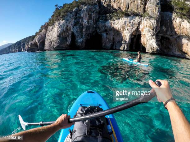 couple stand up paddling - sardinia stock pictures, royalty-free photos & images