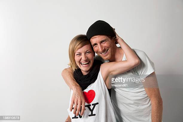 Couple standing against white background, smiling, portrait