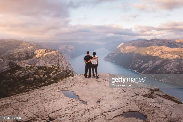 couple standing at cliff at preikestolen, norway during sunset - スタバンゲル ストックフォトと画像