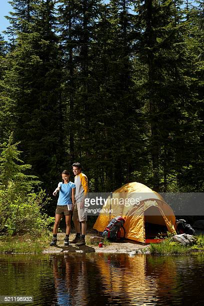 Couple standing at waters edge, by a tent