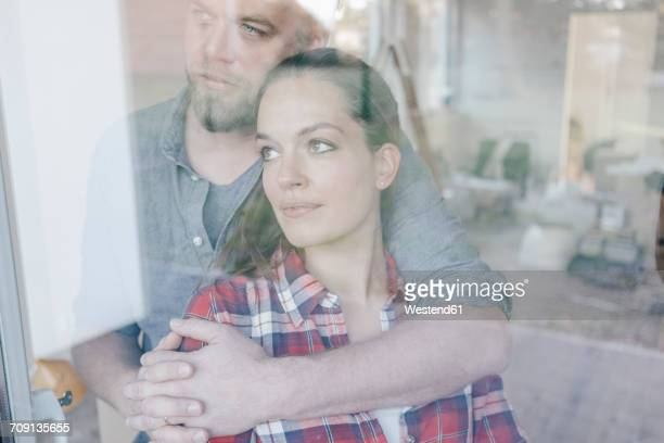 Couple standing at window of their new home
