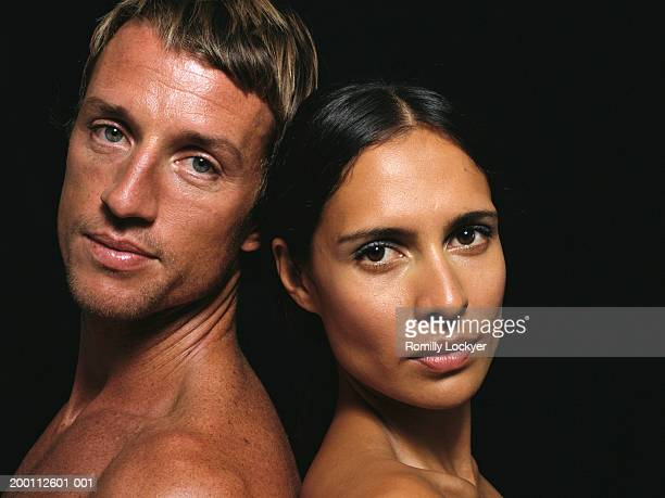 Couple standing back to back against black background, portrait