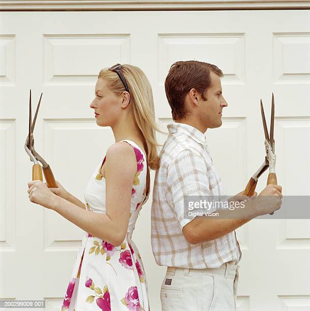Couple standing back to back, holding garden shears, profile