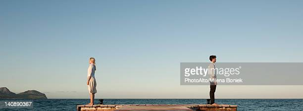 couple standing back to back on pier, side view - middlebare afstand stockfoto's en -beelden