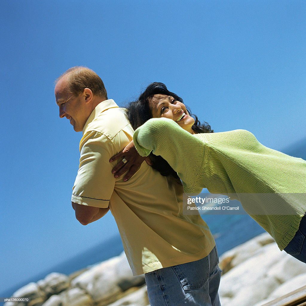 Couple standing back to back outside, smiling : Stockfoto
