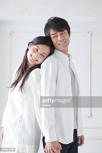 Couple standing back to back, smiling