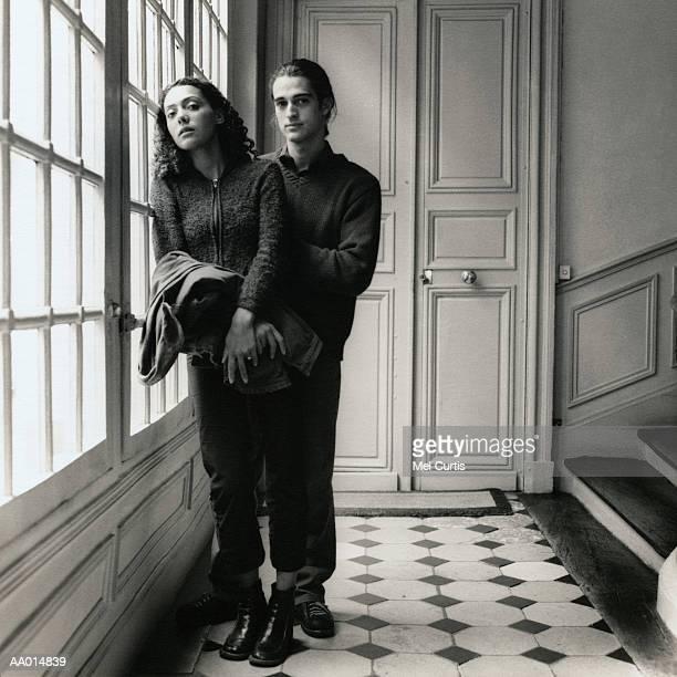 couple standing beside a window on a stairwell - heteroseksueel koppel stockfoto's en -beelden