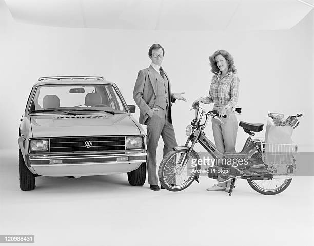 Couple standing beside car and scooter, smiling, portrait