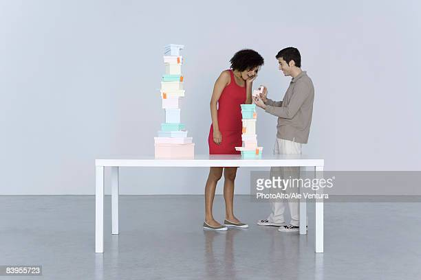 Couple standing beside table stacked with boxes, man giving woman a gift