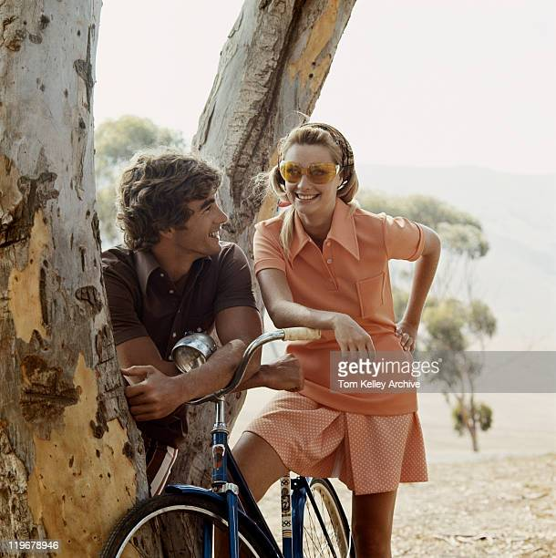 Couple standing beside tree with bicycle
