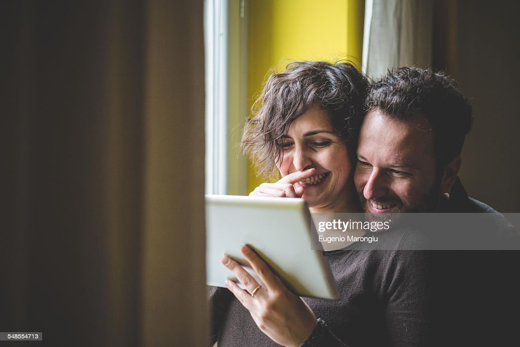 Couple standing beside window, using digital tablet : Stock Photo