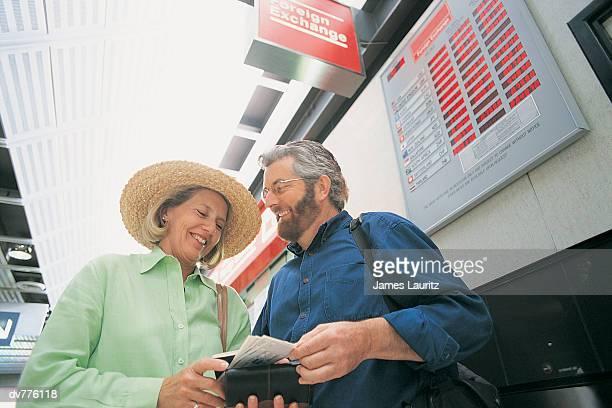 Couple Standing by a Bureau de Change at an Airport