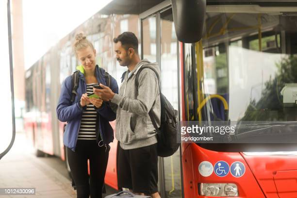 Couple standing by a bus looking at a mobile phone