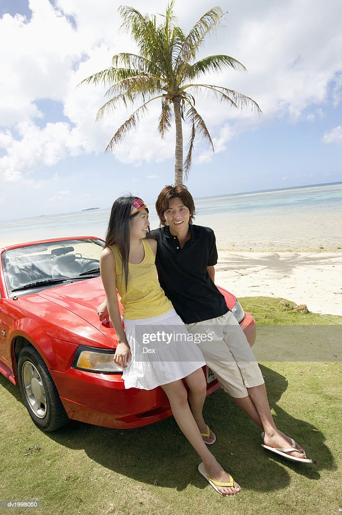 Couple Standing by a Convertible by the Beach : Stock Photo