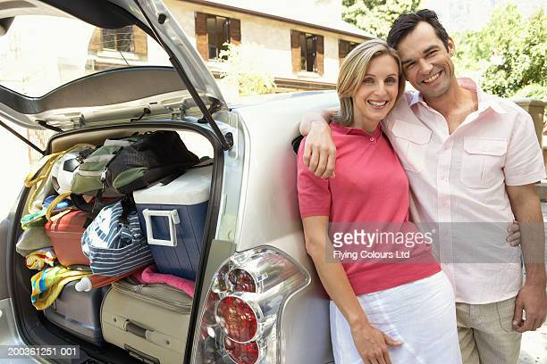 Couple standing by car with luggage, portrait