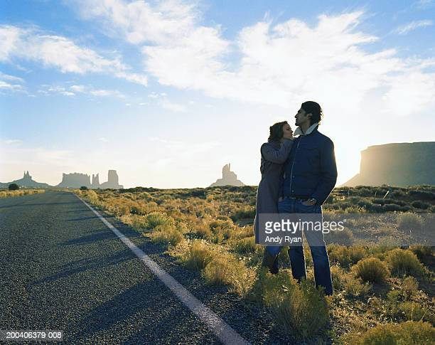 Couple standing by desert road, woman resting on man's shoulder