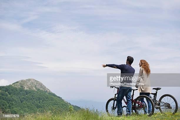 couple standing by mountain bikes enjoying scenic mountain view - ecoturismo foto e immagini stock