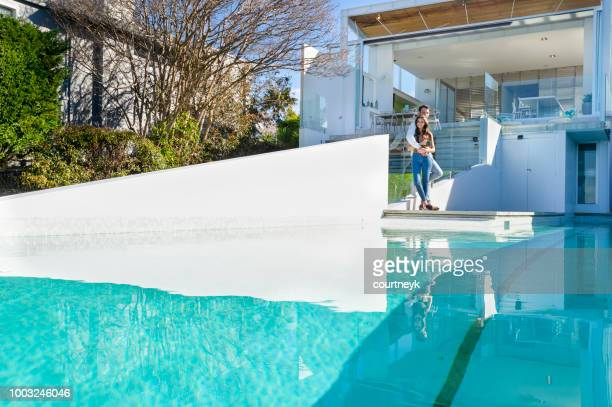 Couple standing by the swimming pool of luxury new house.