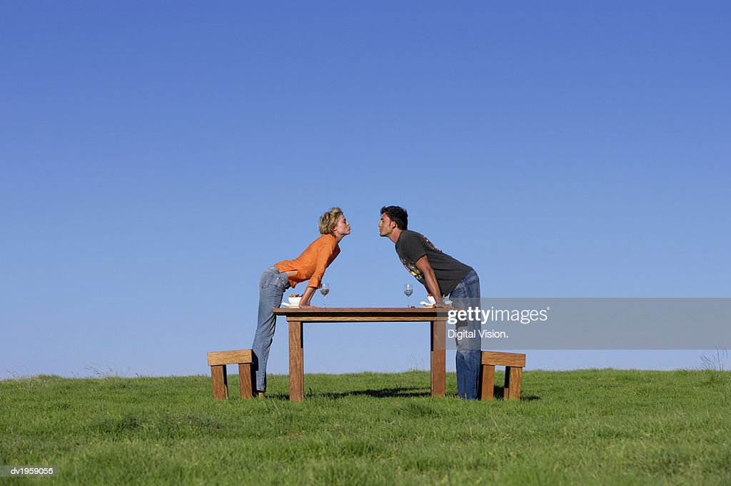 Couple Standing Face to Face and Kissing at a Table on the Grass for Breakfast : Stock Photo