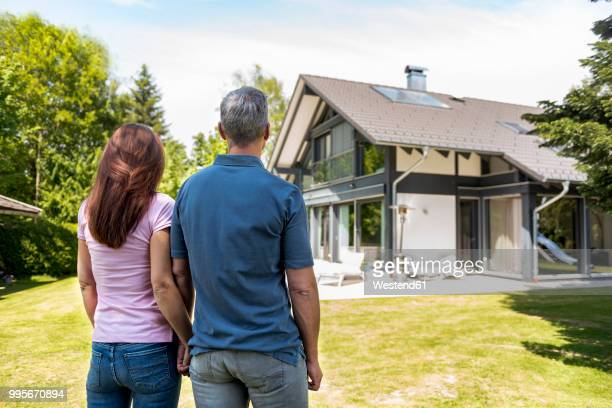 Couple standing hand in hand in garden of their home