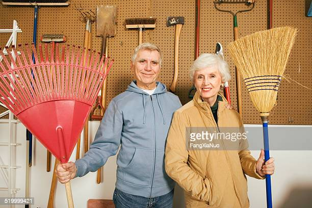 Couple standing , holding  broom, portrait