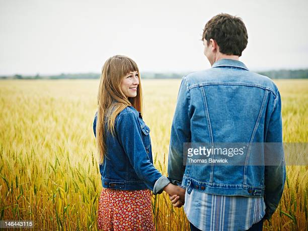 Couple standing holding hands in wheat field