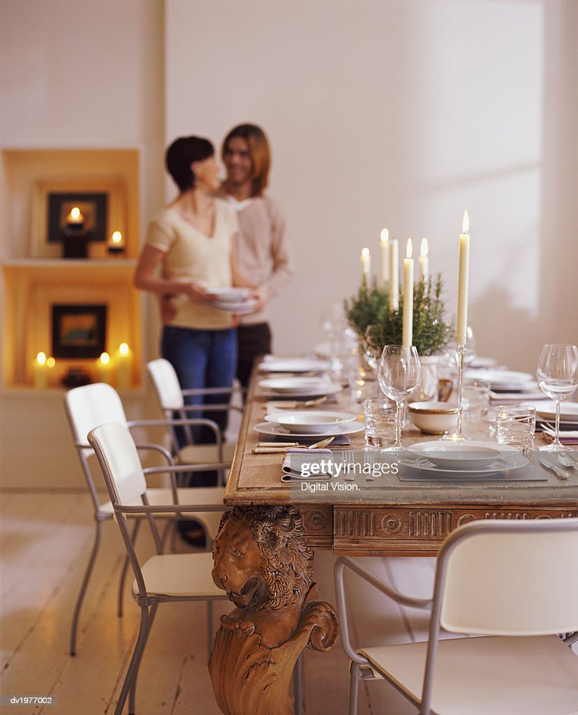 Couple Standing in a Dining Room Next to a Wooden Dining Table : Stock Photo