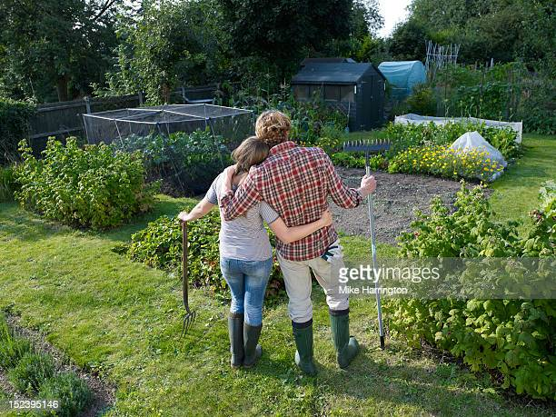 couple standing in allotment - brown hair stock pictures, royalty-free photos & images