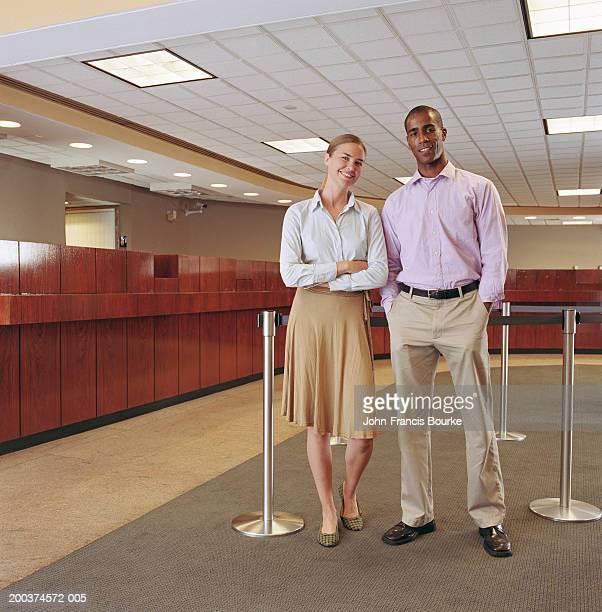 Couple standing in bank, portrait