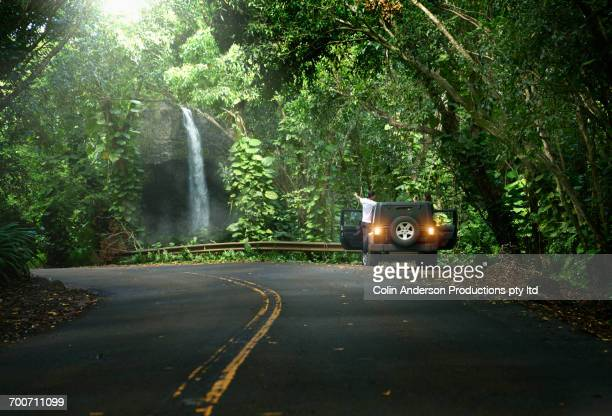 couple standing in car on side of forest road admiring waterfall - water fall hawaii stock pictures, royalty-free photos & images