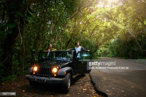 Couple standing in car on side of forest road