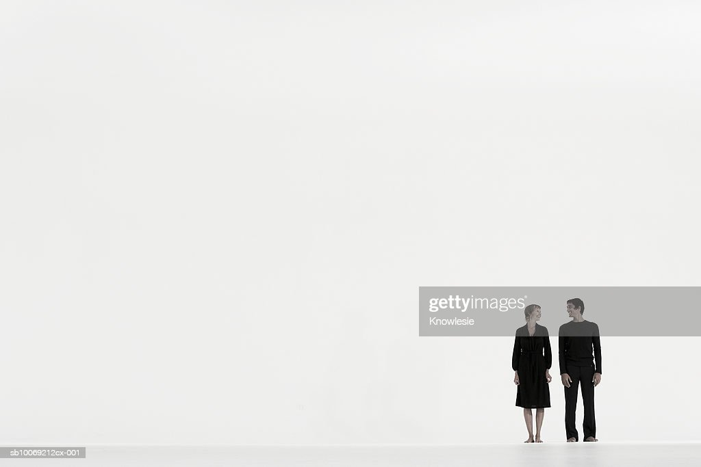 Couple standing in distance against white background, side view : Stockfoto