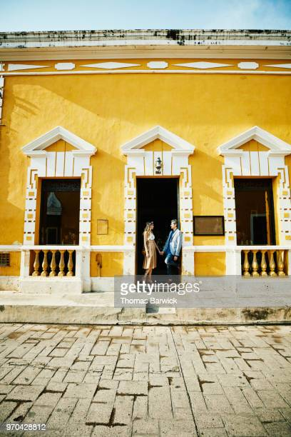 Couple standing in doorway of hotel before exploring town during vacation