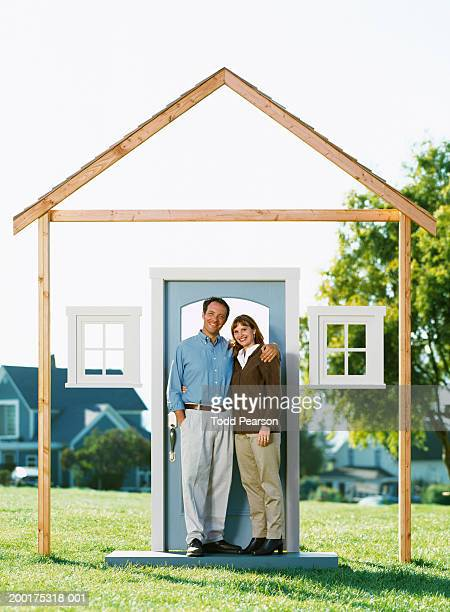 Couple standing in doorway of house framework, portrait