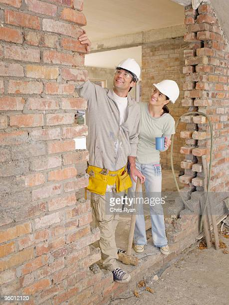 couple standing in doorway of house under construction - mallet hand tool stock pictures, royalty-free photos & images