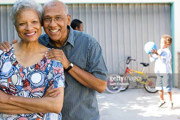 couple standing in driveway with people in background - black granny stock photos and pictures