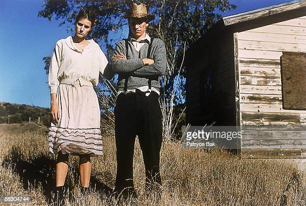 Couple standing in field by shack