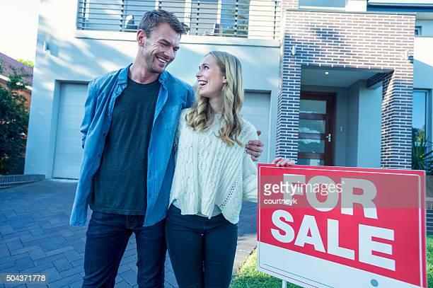 Couple debout devant un nouveau chez-vous.
